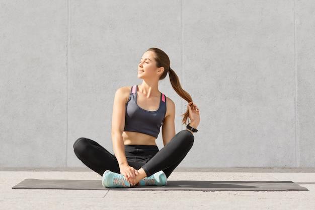 Расслабленная красивая кавказская женщина держит конский хвост, сидит на скрещенных ногах на спортивном коврике