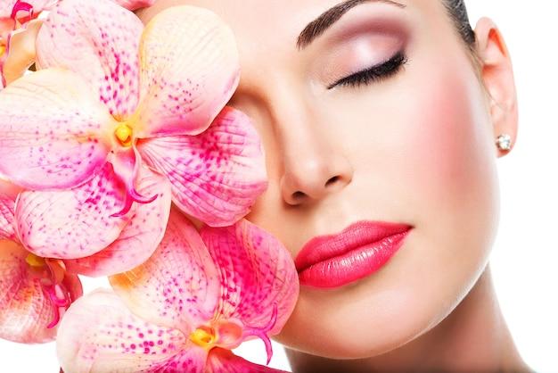 Расслабленное красивое лицо молодой девушки с чистой кожей и розовыми орхидеями. концепция лечения красоты