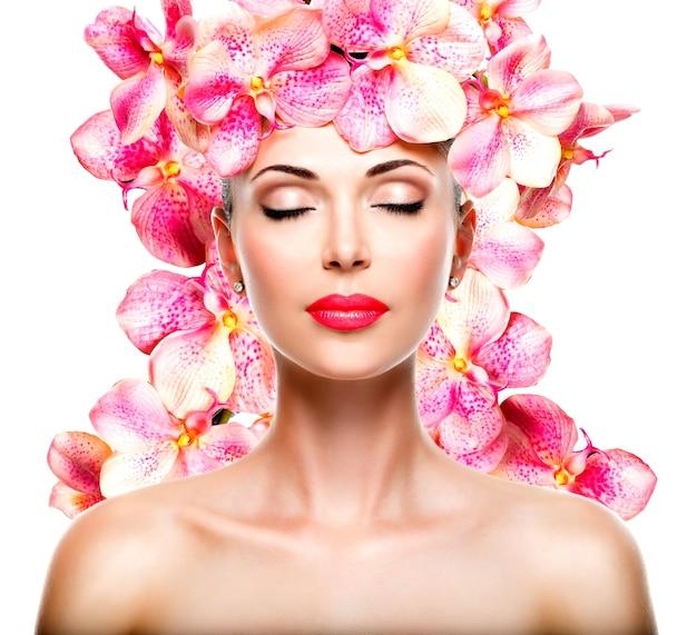 透明な肌とピンクの蘭を持つ少女のリラックスした美しい顔。美容トリートメントのコンセプト