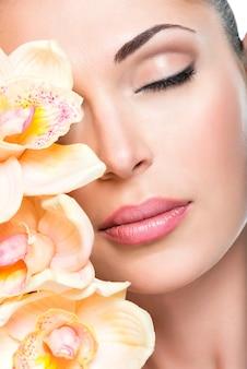 맑은 피부와 분홍색 난초를 가진 어린 소녀의 편안한 아름다운 얼굴. 미용 치료 개념