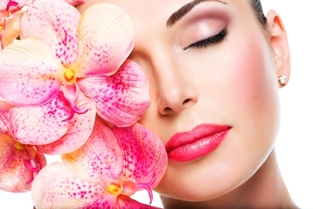 Relaxed beautiful face of a young girl with clear skin and pink orchids. beauty treatment concept