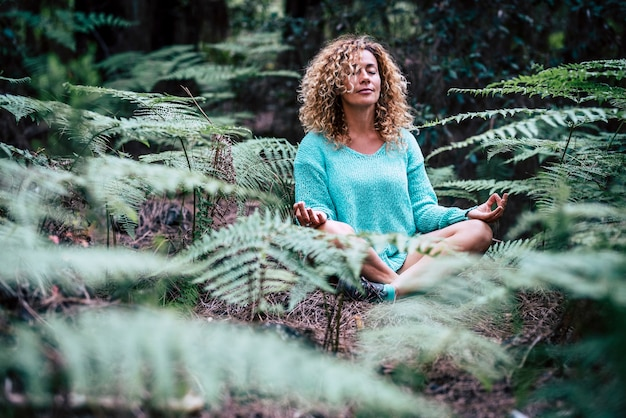 편안한 아름다운 아가씨는 야외 자연 식물 한가운데에 앉아 명상을합니다.