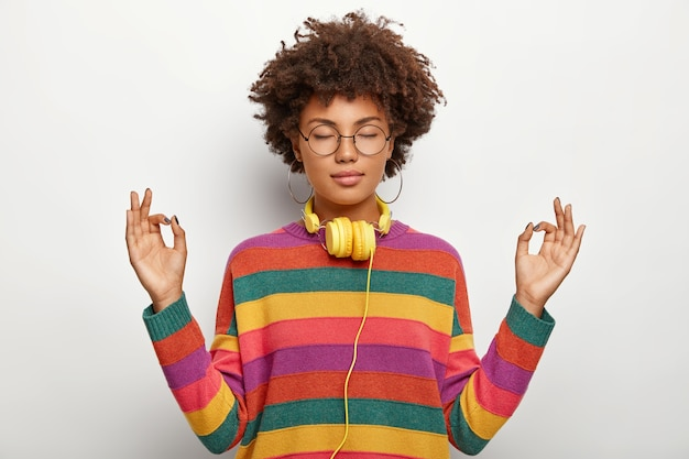 Relaxed beautiful lady with afro hairstyle meditates indoor, keeps eyes closed, feels satisfied lo listen pleasant music in headphones, wears spectacles, earrings, striped jumper. body language