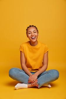 La bella e rilassata donna millenaria siede a gambe incrociate, ride, ha conversazioni esilaranti, indossa maglietta, jeans, calzini, ha un'acconciatura con treccine, isolato sul muro giallo, esprime emozioni spensierate