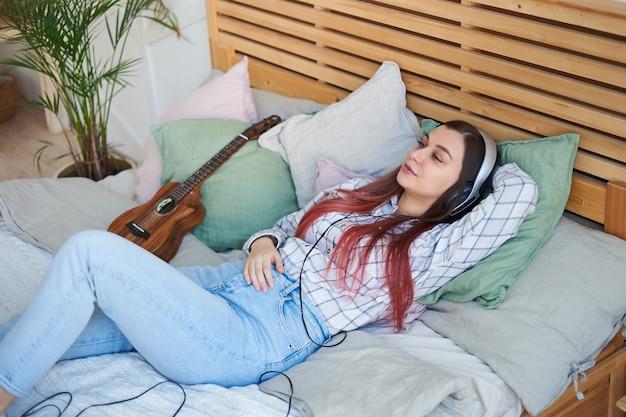 ベッドに横たわってヘッドフォンで音楽を聴いてリラックスした美しい女性。