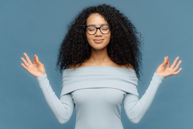 Relaxed beautiful woman with afro hairstyle, feels relieved, shows zen gesture