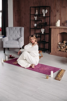 Relaxed beautiful woman with fair hair in white clothes sits on the yoga mat and looks aside