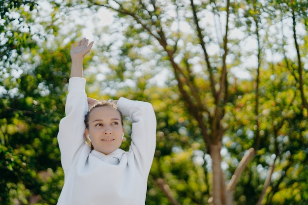 Relaxed beautiful young woman does stretching exercises outdoors keeps arms raised up focused into distance wears white hoodie listens music in earphones has training in park during sunny day