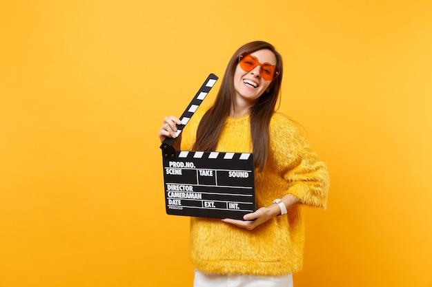 黄色の背景で隔離のカチンコを作る古典的な黒いフィルムを保持しているオレンジ色のハートの眼鏡でリラックスした美しい若い女性。人々の誠実な感情、ライフスタイルのコンセプト。広告エリア。