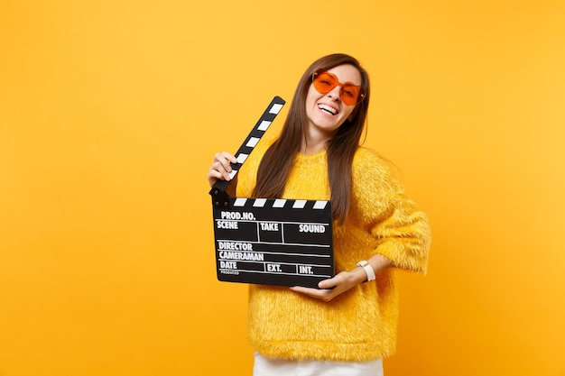 Relaxed beautiful young woman in orange heart eyeglasses holding classic black film making clapperboard isolated on yellow background. people sincere emotions, lifestyle concept. advertising area.