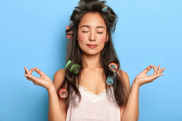 Relaxed beautiful young woman posing with hair curlers