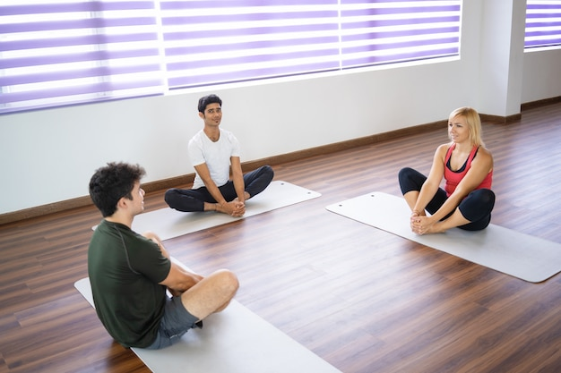 Relaxed beginners sitting on mats and stretching legs
