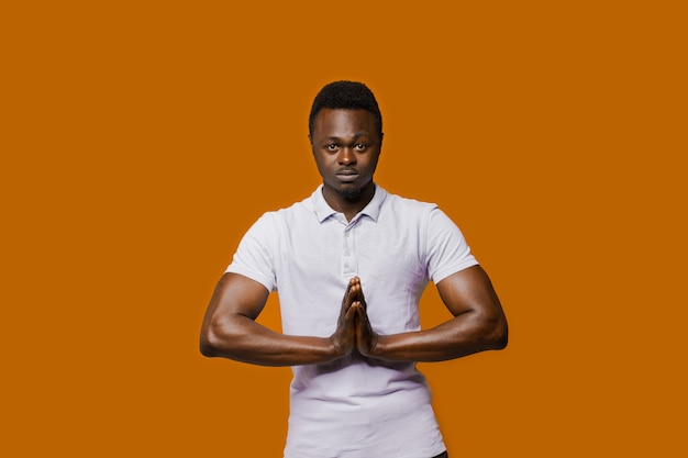 Relaxed black man closes eyes and does yoga. calm and pacification of a african man. public influence on skin color. tolerance to african nationality.