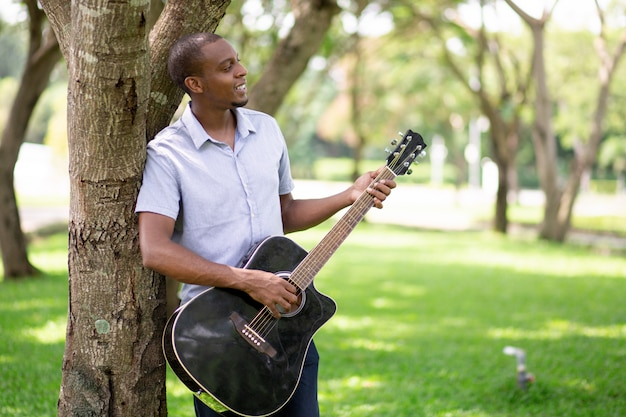 Relaxed black man playing guitar and leaning on tree
