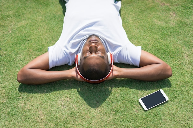 Relaxed black man resting in park and listening to music.
