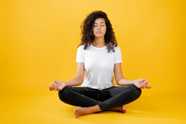 Relaxed black woman meditating in yoga pose isolated over yellow