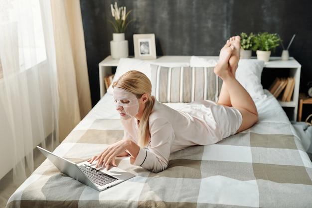 ラップトップとネットワークの前でベッドに横たわっている間、彼女の顔にテキスタイルマスクを持っているシルクパジャマでリラックスしたブロンドの女の子