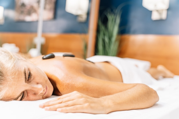 Relaxed blonde girl lying on a massage couch with stones on her back