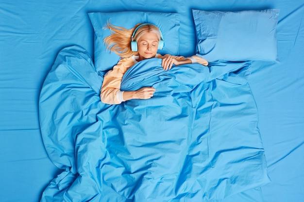 편안한 금발 중간 나이 든 여자가 편안한 침대에서 자고 무선 헤드폰으로 음악을 듣는다.