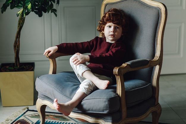 Relaxed boy child in comfortable armchair posing in vintage interior