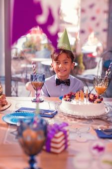 リラックスした男の子。パーティーハットをかぶって、彼の前に大きなケーキを持ってテーブルに座って笑っているポジティブなリラックスした男の子