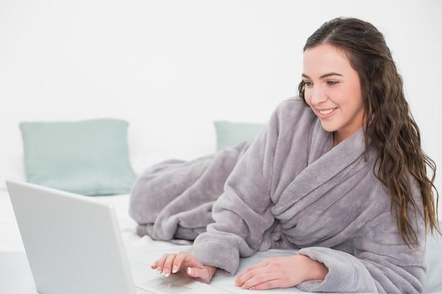 Relaxed brunette in bathrobe using laptop in bed