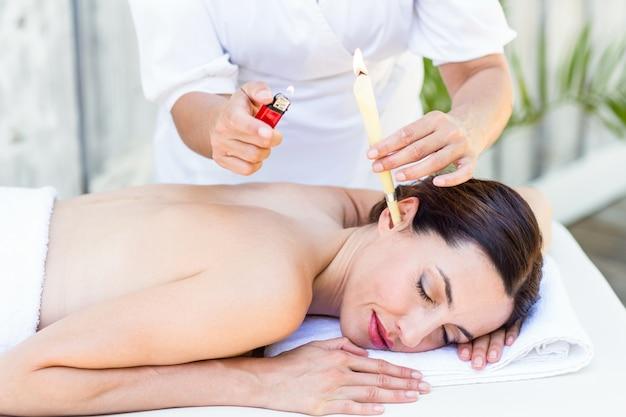 Relaxed brunette getting an ear candling treatment