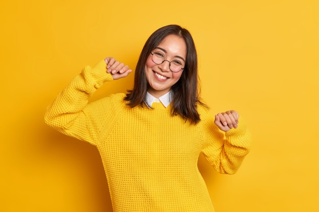 Relaxed brunette pretty woman with eastern appearance raises arms and smiles pleasantly tilts head has positive face expression wears warm jumper.