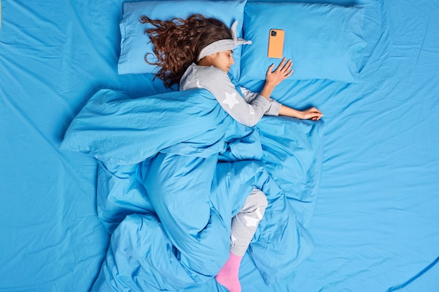Relaxed brunette woman dressed in pajama covered with soft warm duvet has deep sleep at bedroom poses on bed mobile phone lies near has some time before alarm clock. peaceful nap