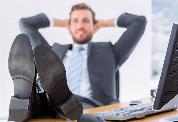 Relaxed businessman sitting with legs on desk