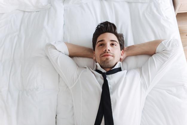 Расслабленный бизнесмен в строгой одежде, лежа на кровати в гостиничной квартире