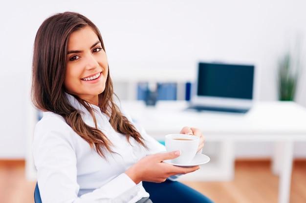 Расслабленная деловая женщина, перерыв и пить кофе