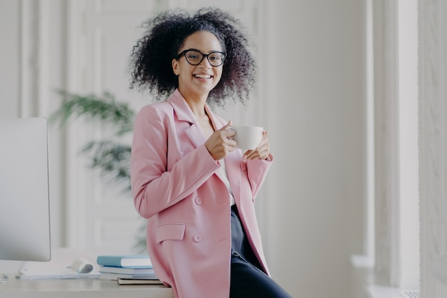 Relaxed businesswoman holds cup of hot drink, has coffee break, stands near her workplace in spacious white cabinet wears spectacles long pink jacket works in office. time for rest after work