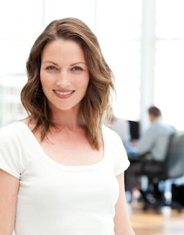 Relaxed businesswoman posing in front of her team