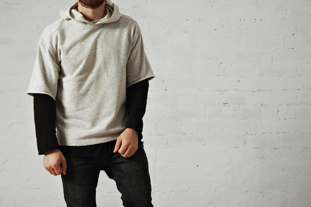 黒のジーンズ、黒の長袖tシャツ、白で隔離の無地のヘザーグレーの快適なパーカーを身に着けているひげを持つリラックスした穏やかな運動の若い男