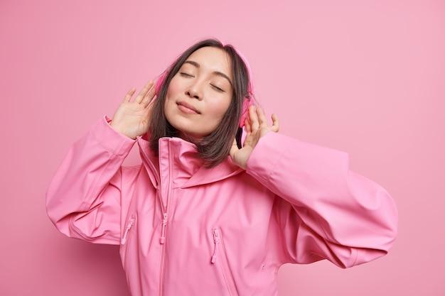 リラックスしたのんきなアジアの女性は、ワイヤレスヘッドホンを着用して目を閉じ、ピンクのジャケットのポーズに身を包んだ歌のリズムを室内で楽しんでいます。モノクロームショット。余暇の生活を楽しむ