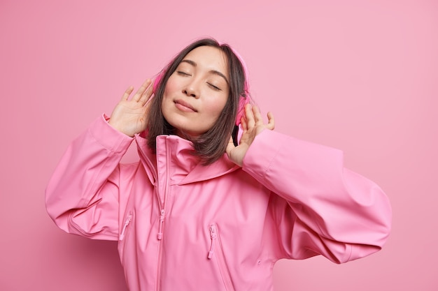 Relaxed carefree asian woman wears wireless headphones closes eyes enjoys favorite music cathes rhythm of song dressed in pink jacket poses indoor. monochrome shot. enjoying life during spare time