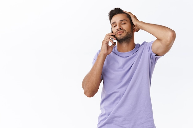 Relaxed and carefree, dreamy gay man in purple t-shirt, brushing hair with fingers relieved, close eyes talking on smartphone, having sensual conversation with boyfriend, like hear his voice