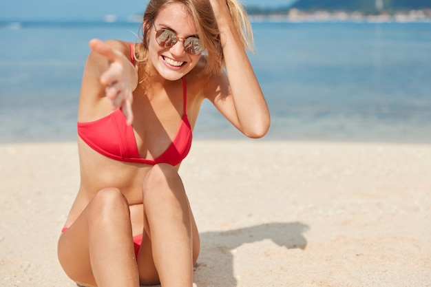 Relaxed carefree female model wears bathing suit and trendy shades, stretches hand, sits on sand against blue water with copy space for your promotional text. people, recreation and lifestyle concept