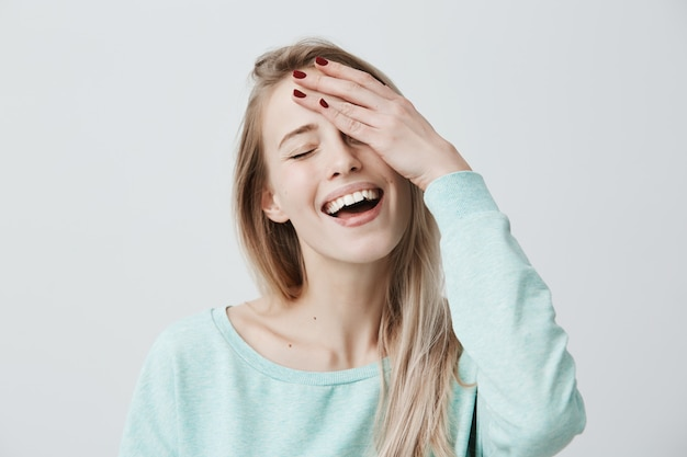 Relaxed carefree woman with blonde hair, closing eyes and smiling broadly, wearing casual clothes, holding hand on head, closing her eyes while dreaming about something pleasant. joy and emotions