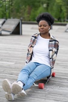 스케이트파크에서 스케이트보드를 탄 후 휴식을 취하는 편안한 캐주얼 아프리카 소녀는 무선 헤드폰 장치를 사용하여 롱보드에 앉아 음악을 듣습니다. 도시 공원 야외에서 청바지에 진정 흑인 여성 젊은 성인