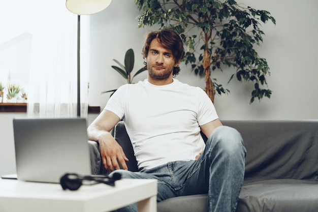 Расслабленный случайный мужчина сидит на диване и смотрит в камеру