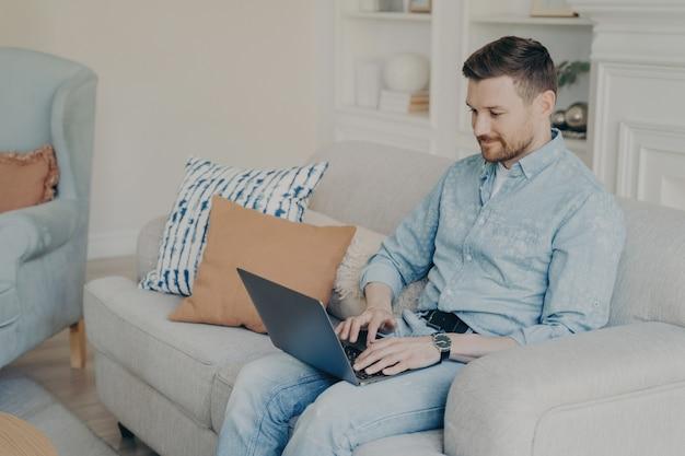 Расслабленный небрежно одетый молодой бизнесмен работает из дома, сидя на удобном диване в светлой гостиной, печатая на ноутбуке и используя специальное программное обеспечение для бизнеса. концепция фрилансера