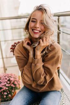 Расслабленная кавказская девушка сидит на балконе утром. очаровательная молодая женщина смеется