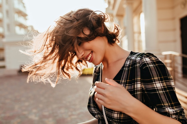 通りで髪を振っているリラックスした白人の女の子。秋の日に屋外に立っている市松模様のシャツを着た笑顔のjocund女性。