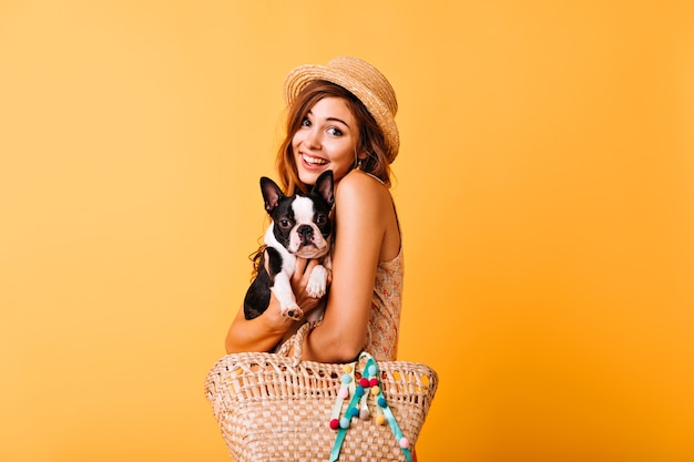 Relaxed caucasian lady embracing her cute dog. excited red-haired girl in straw hat holding french bulldog.