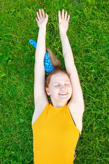 Relaxed caucasian young woman lying on the grass with arms up