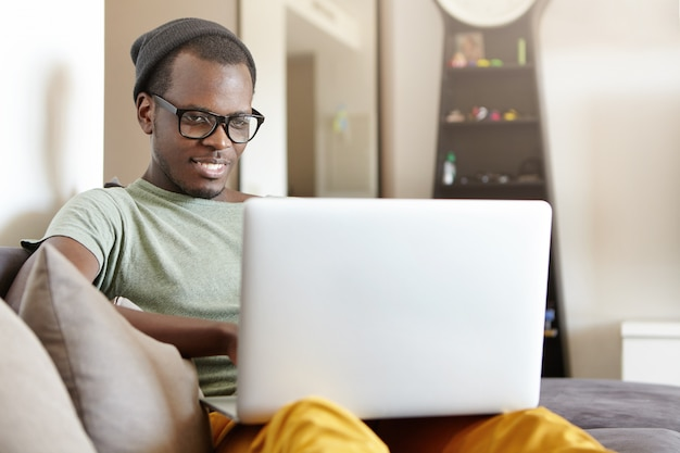 Relaxed cheerful young black european man in stylish eyewear and hat sitting on comfortable sofa at home with laptop pc on his lap, having video call or playing video games online on weekend