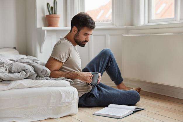 Расслабленный сосредоточенный бородатый парень позирует дома во время работы