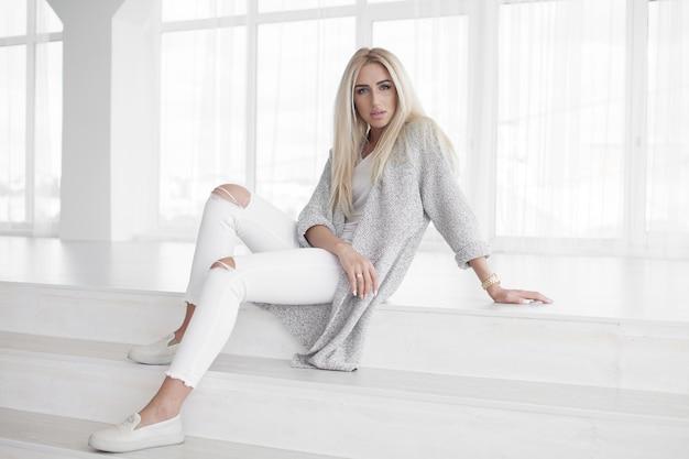 トレンディな白いジーンズの階段に座ってリラックスできる自信を持って若い女性晴れやかなフレンドリーな笑顔